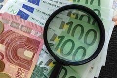 关闭在堆的放大镜与Eur的欧洲钞票 免版税图库摄影
