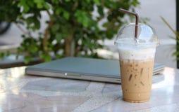 关闭在塑料杯子的冰冻咖啡有棕色秸杆的和聚焦笔记本 免版税库存图片
