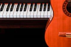 关闭在大平台钢琴钥匙的经典吉他与拷贝空间的音乐背景的 图库摄影
