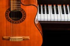 关闭在大平台钢琴钥匙的经典吉他与拷贝空间的音乐背景的 库存照片