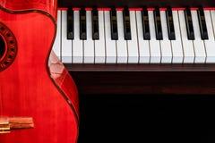 关闭在大平台钢琴钥匙的经典吉他与拷贝空间的音乐背景的 免版税图库摄影