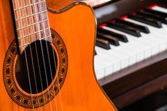 关闭在大平台钢琴钥匙的经典吉他与拷贝空间的音乐背景的 免版税库存图片