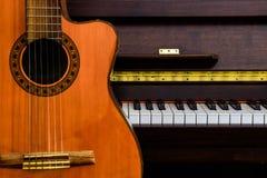 关闭在大平台钢琴钥匙的经典吉他与拷贝空间的音乐背景的 库存图片