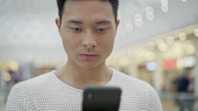 关闭在大购物中心背景的亚洲男性移动的电话 股票视频