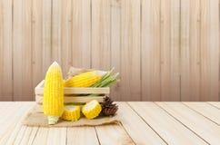 关闭在大麻大袋和木头箱子的新鲜的自然玉米在木flo 库存图片