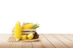 关闭在大麻大袋和木头箱子的新鲜的自然玉米在木flo 免版税库存图片