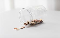关闭在大玻璃瓶子的欧洲硬币在桌上 库存图片