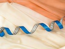 关闭在奶油色和米黄薄纱的蓝色扭转的卷尺有布的 免版税库存图片