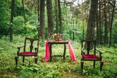 关闭在婚礼装饰的桌上的白色葡萄酒大烛台在桃红色花森林花束  在Th的浪漫晚餐 免版税库存图片