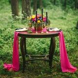 关闭在婚礼装饰的桌上的白色葡萄酒大烛台在桃红色花森林花束  在Th的浪漫晚餐 库存照片