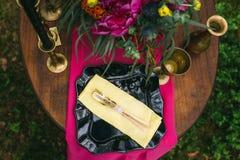 关闭在婚礼装饰的桌上的白色葡萄酒大烛台在桃红色花森林花束  在Th的浪漫晚餐 免版税图库摄影