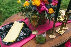 关闭在婚礼装饰的桌上的白色葡萄酒大烛台在桃红色花森林花束  在Th的浪漫晚餐 图库摄影