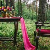 关闭在婚礼装饰的桌上的白色葡萄酒大烛台在桃红色花森林花束  在Th的浪漫晚餐 免版税库存照片