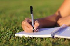 关闭在室外的笔记本的妇女手文字 免版税库存照片