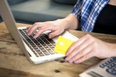 关闭在家举行在线的信用卡在互联网上的妇女的手购物或银行业务有便携式计算机的在国内financ 库存图片