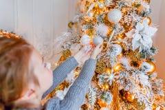 关闭在家装饰圣诞树的女孩手 库存图片