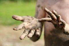 关闭在小男孩的泥泞的手上 免版税库存照片