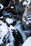 关闭在山流动在岩石之间的溪河盖用雪 库存图片