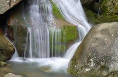 关闭在岩石的缓慢流动的水 图库摄影