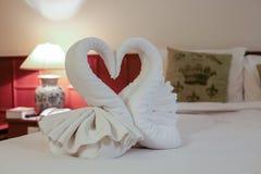 关闭在床上的两只好的毛巾天鹅 免版税库存照片