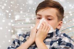 关闭在床和吹的鼻子上的不适的男孩 免版税库存照片