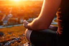 关闭在思考在瑜伽位置的男性手上反对美好的日落 库存图片