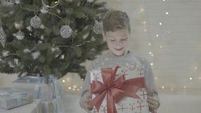 关闭在愉快的孩子在敬畏惊奇的激动的男孩开头圣诞节礼物礼物盒的看法坐在新年树附近 影视素材