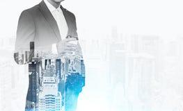 关闭在拿着一杯纸咖啡的衣服的一个商人 有一个城市视图在背景中 免版税库存图片
