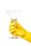 关闭在拿着干净的透明马蒂尼鸡尾酒的黄色防护橡胶手套的女性手玻璃 图库摄影