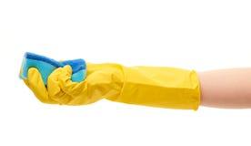 关闭在拿着蓝色清洁海绵的黄色防护橡胶手套的女性手 库存图片