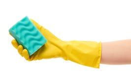 关闭在拿着绿色清洁海绵的黄色防护橡胶手套的女性手 库存照片