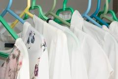 关闭在挂衣架的白色女性衣裳 免版税库存照片