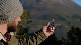 关闭在指南针仪器在手套的手上 山供徒步旅行的小道 前面绊倒概念 股票录像