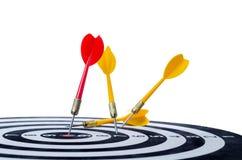 关闭在掷镖的圆靶的中心的射击红色箭箭头并且染黄a 免版税库存图片