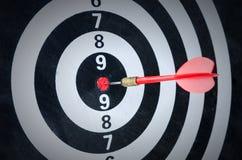 关闭在掷镖的圆靶的中心的射击红色箭箭头 库存图片