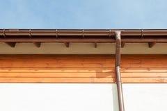 关闭在新的雨天沟,水落管,下端背面板,招牌反对蓝天的板设施 免版税库存照片