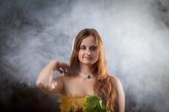 关闭在有由五颜六色的叶子做的长发佩带的礼服的美丽的少女在秋天有薄雾的森林里 免版税库存图片