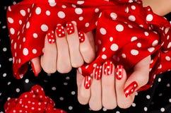 关闭在有逗人喜爱的红色修指甲的美好的女性手上与白色小点。 图库摄影