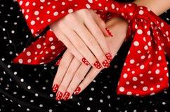 关闭在有逗人喜爱的红色修指甲的美好的女性手上与白色小点。 免版税库存照片