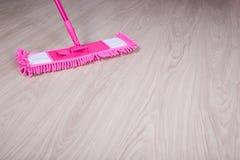 关闭在木地板上的桃红色拖把 免版税库存图片