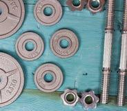 关闭在木地板上的金属重量板材和哑铃在背景中 免版税库存图片