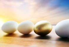 关闭在木头的金黄和白色复活节彩蛋 免版税图库摄影