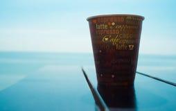 关闭在木日落或日出背景桌和看法上的加奶咖啡杯子  库存图片