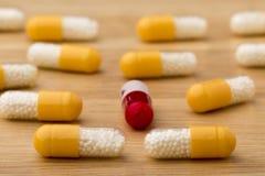 关闭在木桌上的五颜六色的医疗胶囊 免版税图库摄影