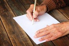 关闭在木桌上的年长男性手。写在白纸 免版税库存照片