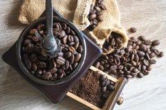 关闭在木磨咖啡器的顶视图烤咖啡豆 库存图片