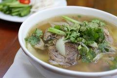 关闭在木背景,牛肉汤面的一个碗中国式 免版税库存图片