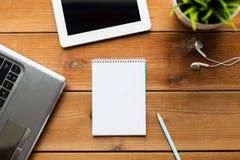关闭在木头的笔记本、膝上型计算机和片剂个人计算机 图库摄影