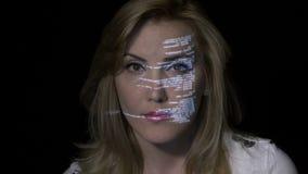 关闭在未来派全息照相的显示的白肤金发的计算机程序设计者女孩编制程序在一个暗室- 股票视频