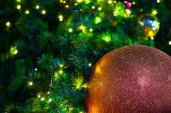 关闭在树的大红色闪烁球圣诞节有导线白光背景 库存图片